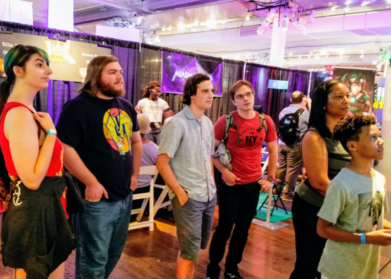 Photo of five people watching a person play Chromavaders